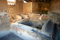 Stone dying baths of the Fullery of Stephanus on the Via del Abbondante, Pompeii. Fulleries were an important business in ancient Pompeii.  Fullers processed, dyed, and washed cloth.