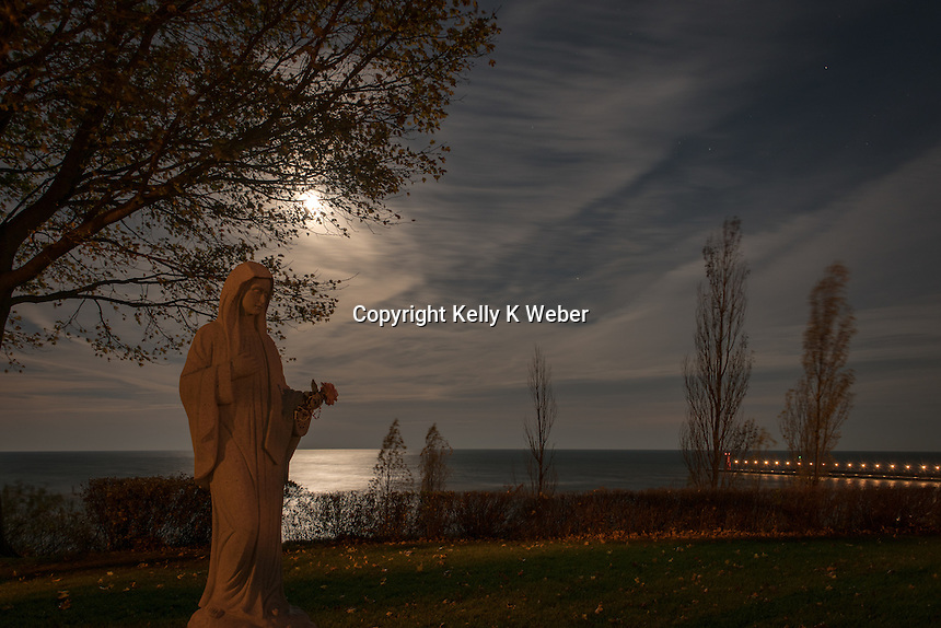 Super moon setting on Lake Michigan early morning in South Haven November 14th, 2016. Closest to the earth until 2034. Statue of Mary on the bluff.