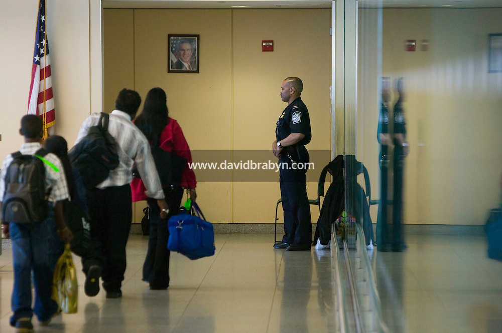 11 April 2006 - New York City, NY - A family (L) heads to the secondary passport control area as a CBP officer stands guard at JFK airport in the Queens borough of New York City, USA, 11 April 2006.