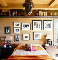 In the guest room the photographs arranged againt the vintage grass-cloth wall-covering above the bed include works by Maury Hopson, Horst and Matthew Roberston