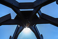 At its center, a wooden sculpture combines radiating wooden beams with a radiating sunburst against a blue sky.  The scene near the playground at a neighborhood park.