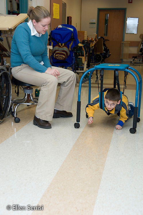 MR / Albany, NY.Langan School at Center for Disability Services .Ungraded private school which serves individuals with multiple disabilities.Teacher supervises child using a belly crawler as he crawls down the hall. Student is weaing a SWASH (sitting, walking, and standing hip apparatus) on his hips / legs. Boy: 9, cerebral palsy, limited verbal output with expressive and receptive language delays.MR: Ris4; Rub1.© Ellen B. Senisi