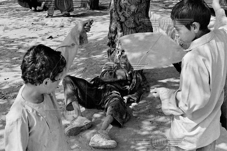 A tramp lies in the street while two boys indulge in kite flying, their favourite pastime.