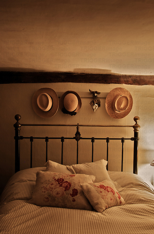 Floral cushions on striped bedding on old iron double bed with straw hats hanging above with silver heart