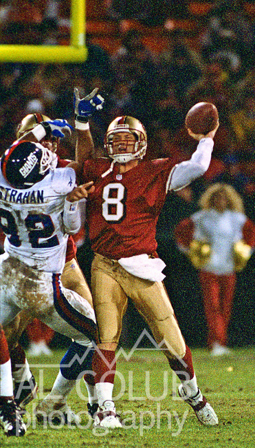 San Francisco 49ers vs. New York Giants at Candlestick Park Monday, November 30, 1998.  49ers beat Giants  31-7.  San Francisco 49ers quarterback Steve Young (8) makes pass as New York Giants defensive end Michael Strahan (92) attempts to stop him.