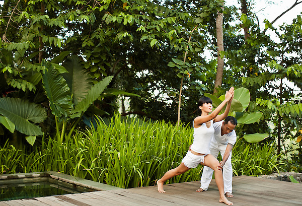 A woman practices yoga during a privtae teaching session in a pool villa at Kayumanis Ubud, Bali, Indonesia.