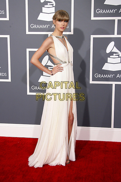 Taylor Swift.The 55th Annual GRAMMY Awards held at STAPLES Center, Los Angeles, California, USA..February 10th, 2013.grammys full length white silver gold side straps dress hands on hips fringe bangs hair cut out away pleats pleated slit splits.CAP/ADM.©AdMedia/Capital Pictures.