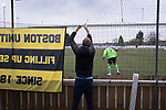 A visiting supporter tying a flag to fencing before Atherton Collieries played Boston United in the FA Trophy third qualifying round at the Skuna Stadium. The home club were formed in 1916 and having secured three promotions in five season played in the Northern Premier League premier division. This was the furthest they had progressed in the FA Trophy and defeated their rivals from the National League North by 1-0, Mike Brewster scoring a late winner watched by a crowd of 303 spectators.