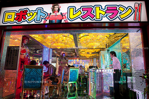 July 23 2012, Tokyo, Japan - From the outside people can see inside the restaurant, where customers are having fun watching the female robot in place and other entertainment. The restaurant advertises that cost 10 billion yen (130 million) opening. Robots run by real women dressed in military, perform cabaret dance for its customers, opened in the Kabukicho area, Shinjuku in Tokyo. (Photo by Rodrigo Reyes Marin/AFLO)