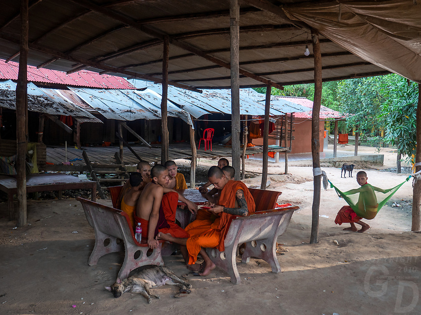 Monastery near the Bayon Temple, Angkor area, Siem reap, Cambodia Monks gathering around the table, note the Tattoos, dogs and cellphone.