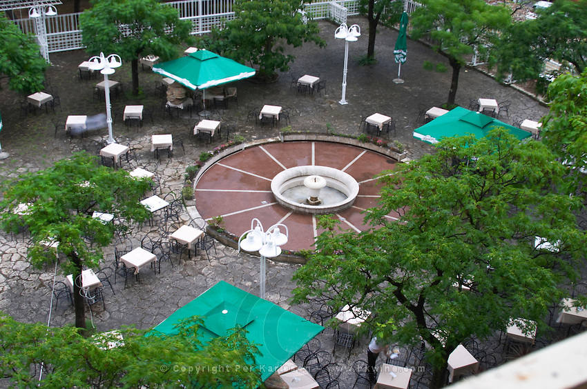The courtyard of the Hotel Crna Gora when it rains. Tables and chairs forming pattern. Podgorica capital. Montenegro, Balkan, Europe.