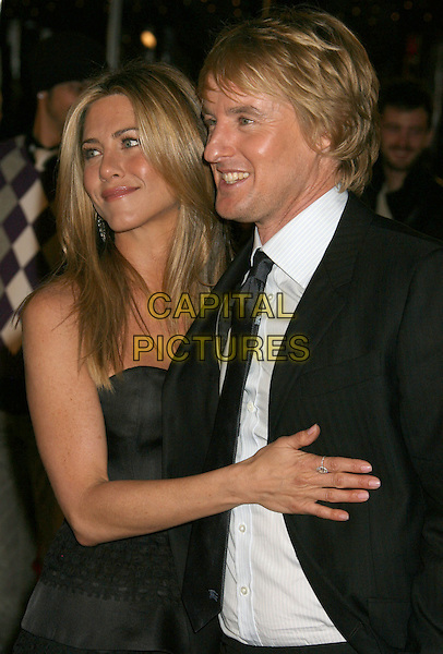 "JENNIFER ANISTON & OWEN WILSON.""Marley & Me"" Los Angeles Premiere held at the Mann Village Theater, Westwood, California, USA..December 11th, 2008.half length black grey gray strapless silk satin top skirt dress frills ruffled ruffles blue tie white shirt suit jacket ring hand on chest stomach.CAP/ADM/MJ.©Michael Jade/AdMedia/Capital Pictures."