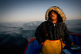 MEXICO, Baja, Magdalena Bay, Pacific Ocean, Enrique's son steering the boat during a grey whale watching tour in the bay