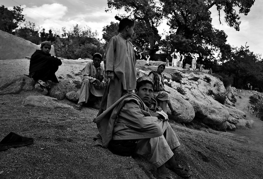 Children watch as members of 2nd Platoon, Bravo Company, 1-32 Infantry, 3rd Brigade, 10th Mountain Division, patrol the bazaar in Charkh, Afghanistan, Saturday, May 9, 2009.