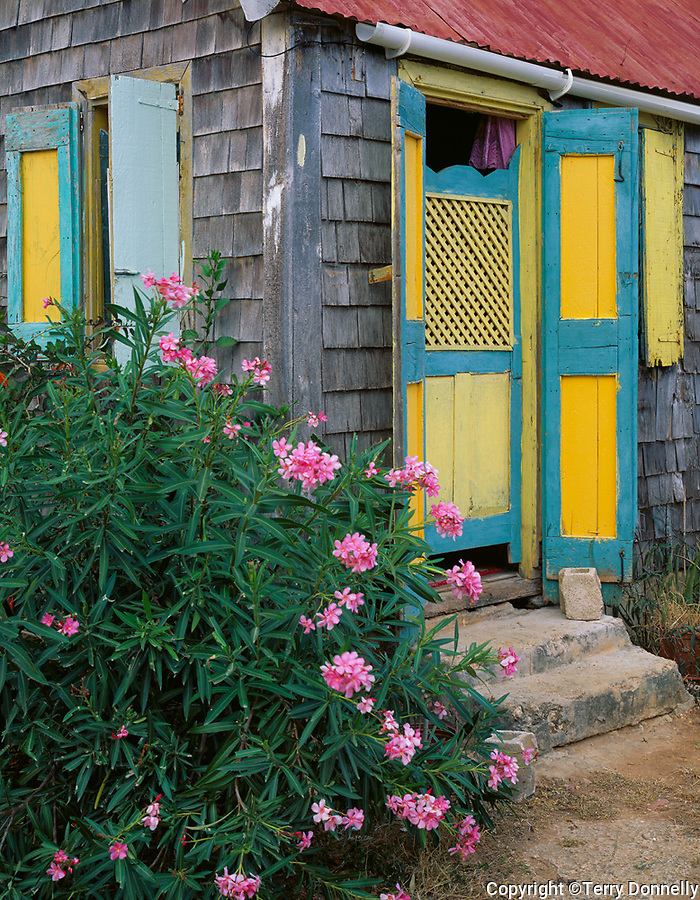 Anguilla, BWI<br /> Weathered wood house with blue and yellow shuttered windows in Anguilla's village of Island Harbor