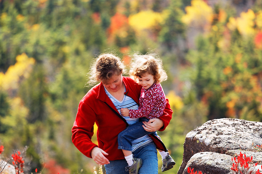 Woman carrying little girl in fall colored landscape, Mount Desert Island, Acadia National Park, near Bar Harbor, Maine, USA