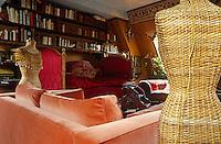 Two wicker dressmaker's dummies flank an orange velvet sofa in the book-lined living room