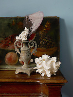 A still life of shells and coral in an antique urn is displayed on a table top
