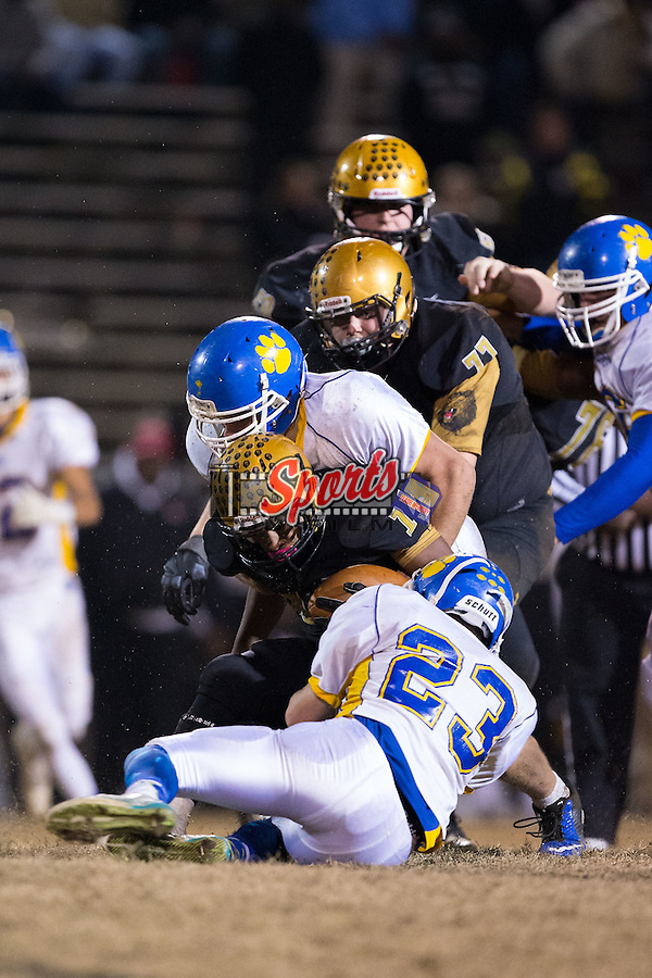 Xavier Brooks (14) of the Shelby Golden Lions is tackled by Dylan Reece (23) and Dakota Wensil (32) of the Mount Pleasant Tigers during first half action at George Blanton Memorial Stadium November 27, 2015, in Shelby, North Carolina.  The Golden Lions defeated the Tigers 38-27.  (Brian Westerholt/Sports On Film)
