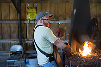 NWA Democrat-Gazette/CHARLIE KAIJO Tanner Sjo of Siloam Springs heats iron at the Tired Iron of the Ozarks in Gentry, AR on Friday, September 7, 2017. The show features old time Tractors and Engines and exhibitions of old-time saw milling and blacksmith work.