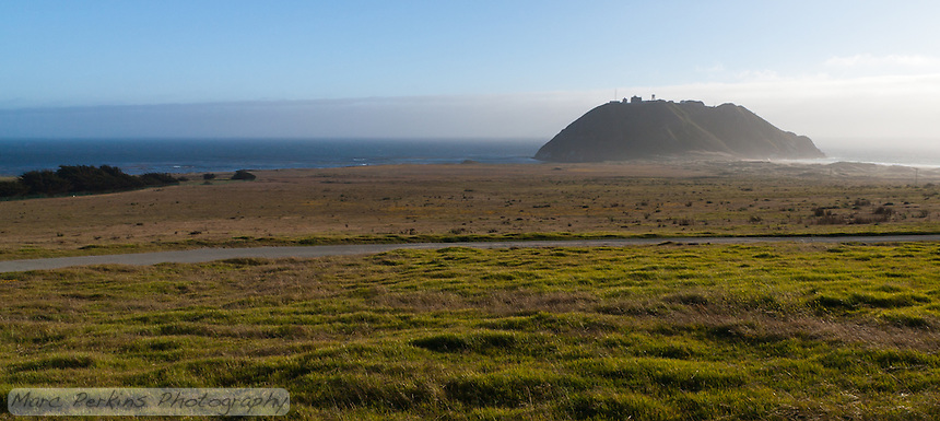 Point Sur Light Station seen from along California Highway 1 (Pacific Coast Highway).  The station's buildings are all on top of the small hill / rock that rises from the ocean behind a grassy meadow on this blustery day.