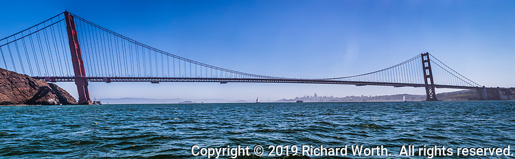 Panoramic image of the Golden Gate Bridge with the San Francisco skyline in the distance.