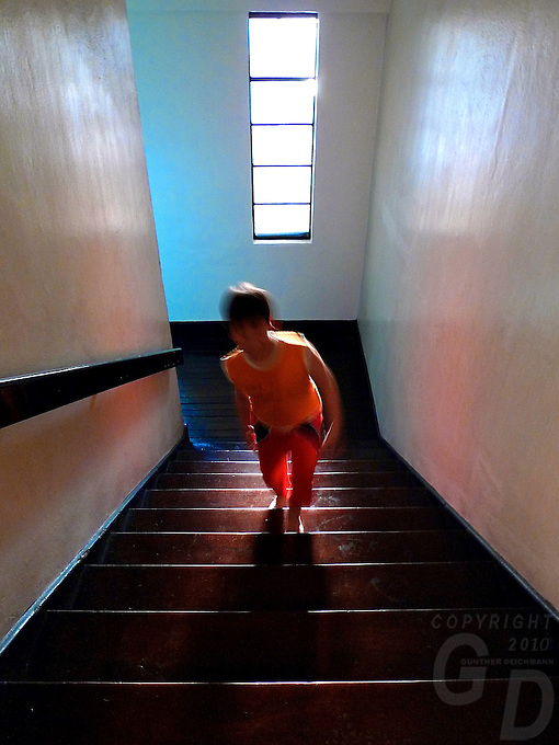 Boy walking up the stairs in an old Building