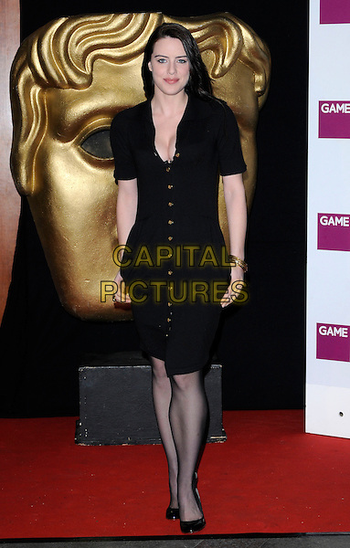 MICHELLE RYAN .At the British Academy Video Games Awards, London HIlton Hotel, Park Lane, London, England, UK, March 19th 2010..BAFTA full length black shirt dress gold brass buttons cleavage hands in pockets tights shoes patent .CAP/CAN.©Can Nguyen/Capital Pictures