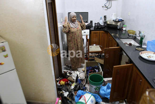Palestinian Mother of Eyad Terawe checks the damage to her family home after Israeli troops arrest her son at the Balata refugee camp near the West Bank city of Nablus, 17 June 2014. Large numbers of Israeli soldiers raided the northern West Bank city of Nablus and its surroundings early 17 June 2014 in the search of three teenagers, three teenagers - Eyal Yifrah, 19, Gilad Shaar, 16, and Naftali Frenkel, 16 - missing since 08 JUne 2014, near the Gush Etzion settlement bloc, north of Hebron. Photo by Nedal Eshtayah