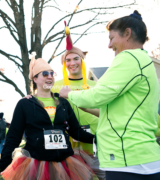 Southbury, CT- 26 November 2015-112615CM02-  Colleen and Michael Harmon of Boston MA, left, warm up with Kathleen Davey of Southbury, during the annual Southbury Women's Club Turkey Trot on Thursday.  Over 2,000 runners completed in the event, which will benefit local charities including the Southbury Food, Southbury Needy Fund and the Fuel Banks.    Christopher Massa Republican-American