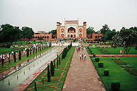 The gardens of the Taj Mahal, green against the red stone of the buildings during a sudden rainstorm, Agra, India.