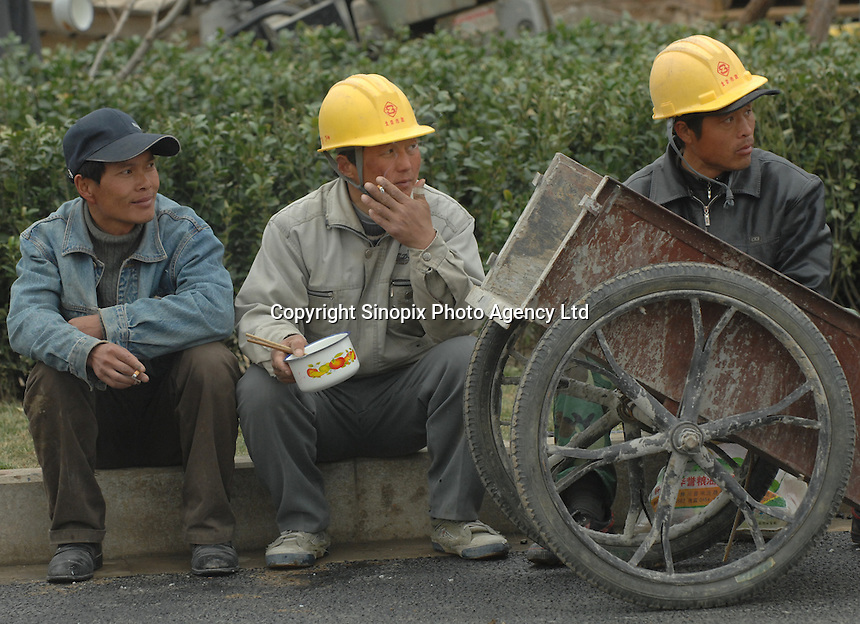 Workers from the Olympic park stop for a lunch break outside the Bird Nest stadium in Beijing, China. Workers are finished the olympic venues on time schedule..