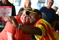 Aug. 1, 2014; Kent, WA, USA; NHRA top fuel dragster driver Antron Brown (right) takes a photo with a fan prior to qualifying for the Northwest Nationals at Pacific Raceways. Mandatory Credit: Mark J. Rebilas-USA TODAY Sports