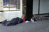 Two homeless men sleeping outside a building in Vancouver, British Columbia, Canada