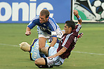 July 22 2007:  Herculez Gomez (r) of the Rapids slides past Kevin Hartman (1) of the Wizards after Hartman intercepted the ball, while Jimmy Conrad (12) of the Wizards begins to go down after Gomez backhanded Conrad in the nose.  The Rapids were awarded and scored a PK on this play.  The MLS Kansas City Wizards tied the visiting Colorado Rapids 2-2 at Arrowhead Stadium in Kansas City, Missouri, in a regular season league soccer match.
