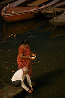"At the ghats of Varanasi Hindu devotees performing the ""Puja"" with lighted lamps Varanasi Ganges India"