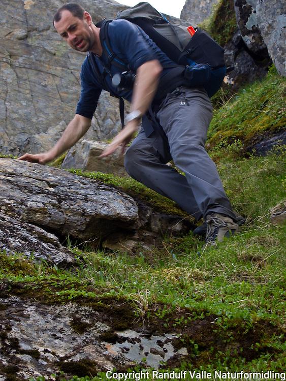 Mann beveger seg ned en bratt passasje. ---- Man climbing down a steep section.