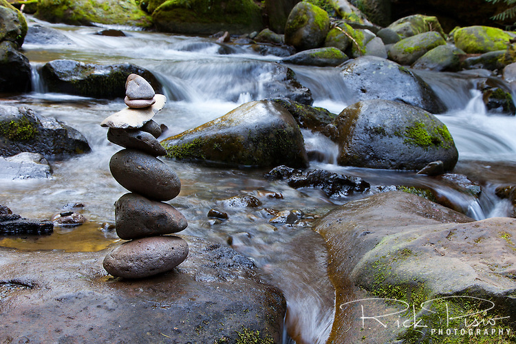 A rock cairn stands alongside the flowing Multnomah Creek above Multnomah Falls in Northern Oregon