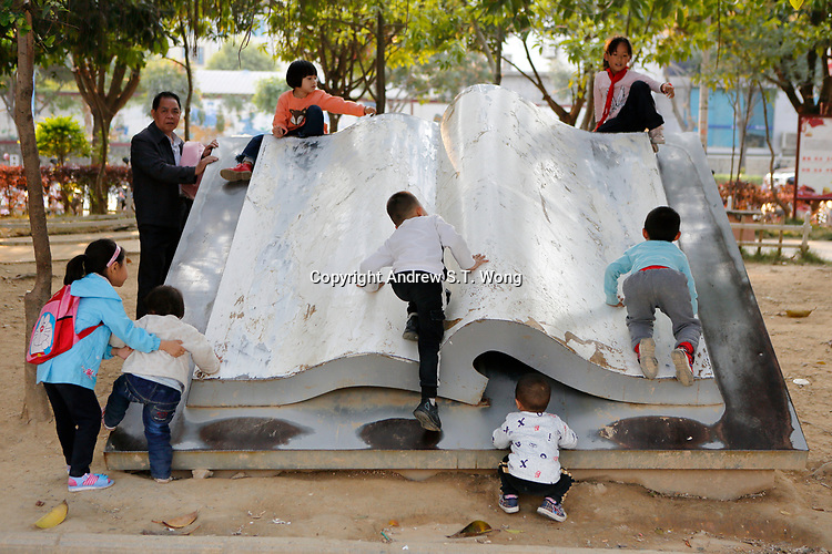 Children of the ethnic Bouyei Tribe play on a stone statue in the shape of a giant book at Wangmo County in China's southwestern Guizhou Province, April 2019.