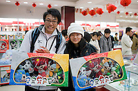 Couple hold boxes of 2008 Olympic Games Fuwa mascot characters in souvenir shop, Wangfujing Street, China