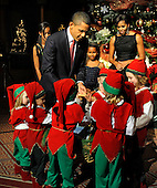 United States President Barack Obama and a group of children dressed as Christmas elves carry a basket for a group photo with First Lady Michelle Obama at a Christmas In Washington celebration at the Building Museum in Washington, DC, USA, Sunday, December 12, 2010.  Obama's daughters Malia and Sasha are at (L) in the background.     .Credit: Mike Theiler - Pool via CNP