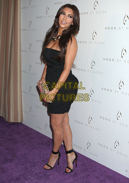 Kim Kardashian.'Noon by Noor' Launch Event held at the Sunset Tower Hotel, West Hollywood, California, USA..July 20th, 2011.full length black strapless dress skirt top circles necklace gold blue open toe sandals beige clutch bag side.CAP/ADM/RE.©Russ Elliot/AdMedia/Capital Pictures.