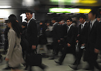 Businessmen rush through an underground walkway in Shinjuku Station, Tokyo, Japan.  With up to 4 million passengers passing through it every day, Shinjuku station, Tokyo, Japan, is the busiest train station in the world. The station was used by an average of 3.64 million people per day.  That's 1.3 billion a year.  Or a fifth of humanity. Shinjuku has 36 platforms, and connects 12 different subway and railway lines.  Morning rush hour is pandemonium with all trains 200% full. <br /> <br /> Photo by Richard jones / sinopix