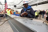 Workers sign the last piece of steel prior to it being placed during the topping off ceremony at Red Bull Arena in Harrison, NJ, on April 14, 2009.