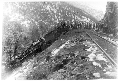 Engine and tender derailed and on steep downslope next to track.  Snow on ground and many people on track inspecting wreck.<br /> D&amp;RG