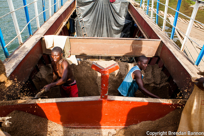 Men shovel sand from a cargo boat at a small port in Kibuye, Rwanda on Lake Kivu. Brendan Bannon. March 1, 2014