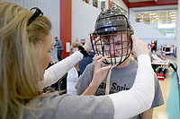 NWA Democrat-Gazette/DAVID GOTTSCHALK Ethan Sligar, an eighth grade student at Siloam Springs Middle School, is assisted by his coach Tami Stallbories with his helmet Friday, February 8, 2019, during a game of floor hockey at the Winter Special Olympics at the Jones Center in Springdale. Twenty three teams statewide participated in the Olympic games sponsored in part by the Law Enforcement Torch Run.