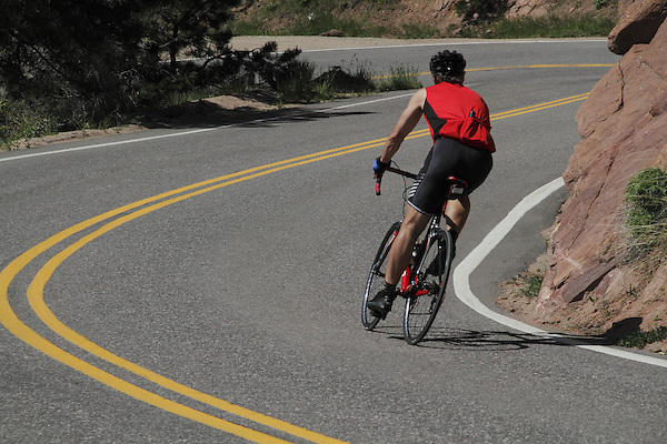 Man biking downhill on Lookout Mountain Road west of Denver, Colorado. .  John leads private photo tours in Boulder and throughout Colorado. Year-round.