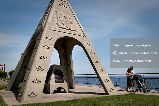Innus walks by a tipi-shaped artwork on a promenade facing the lac St-Jean lake in the innu (Montagnais) reserve of Mashteuiatsh (also called Pointe-Bleue) in the province of Quebec, Canada. the reserve is the home of almost 2000 Innu-Montagnais.