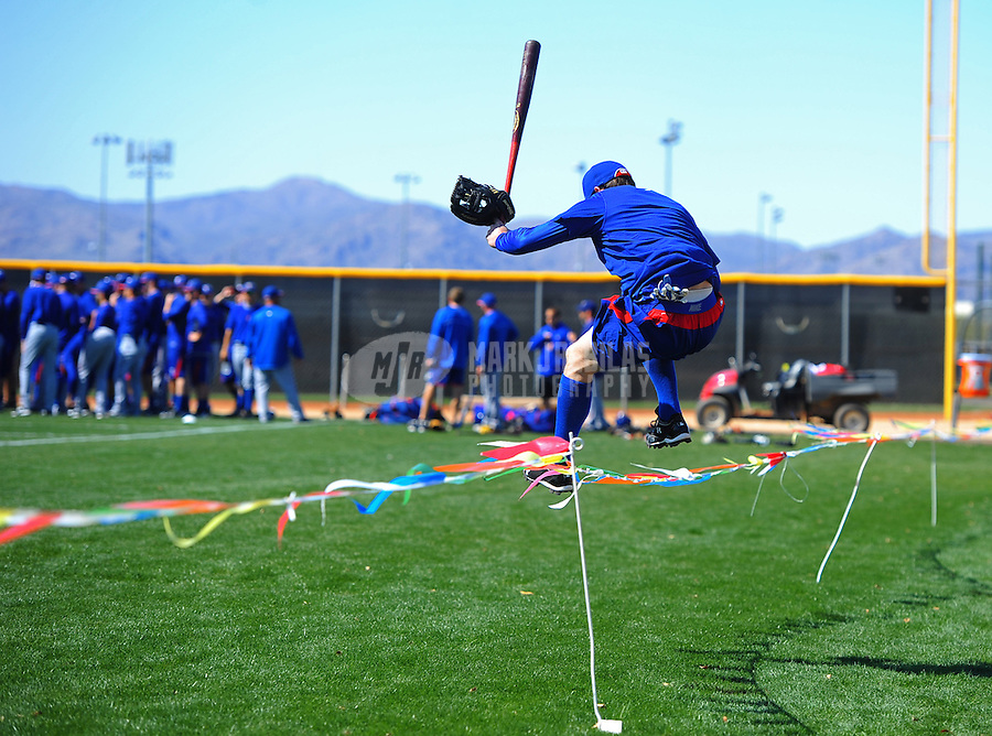 Mar. 2, 2012; Surprise, AZ, USA; A Texas Rangers player leaps over ropes as he heads on the field to stretch prior to an intrasquad game on the practice fields at Surprise Stadium.  Mandatory Credit: Mark J. Rebilas-.